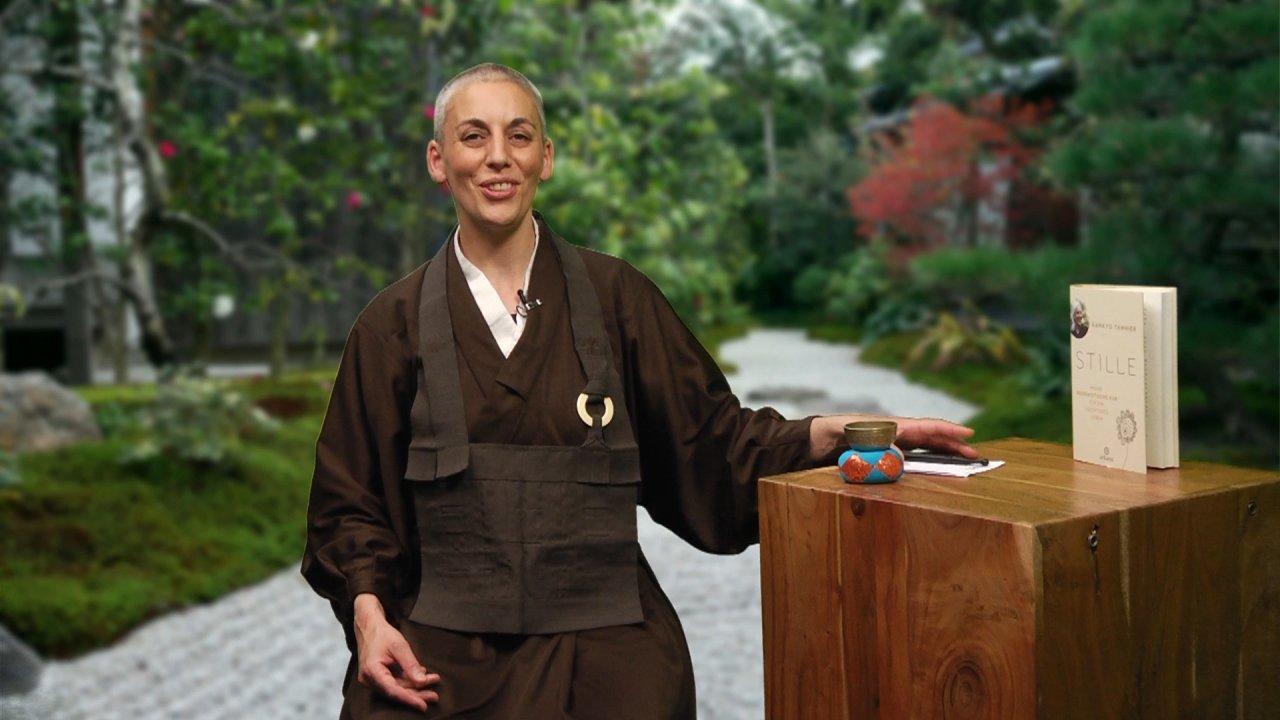 Nonne Kankyo Tannier steht in einem Garten und hat die linke Hand auf einen Holztisch gelegt
