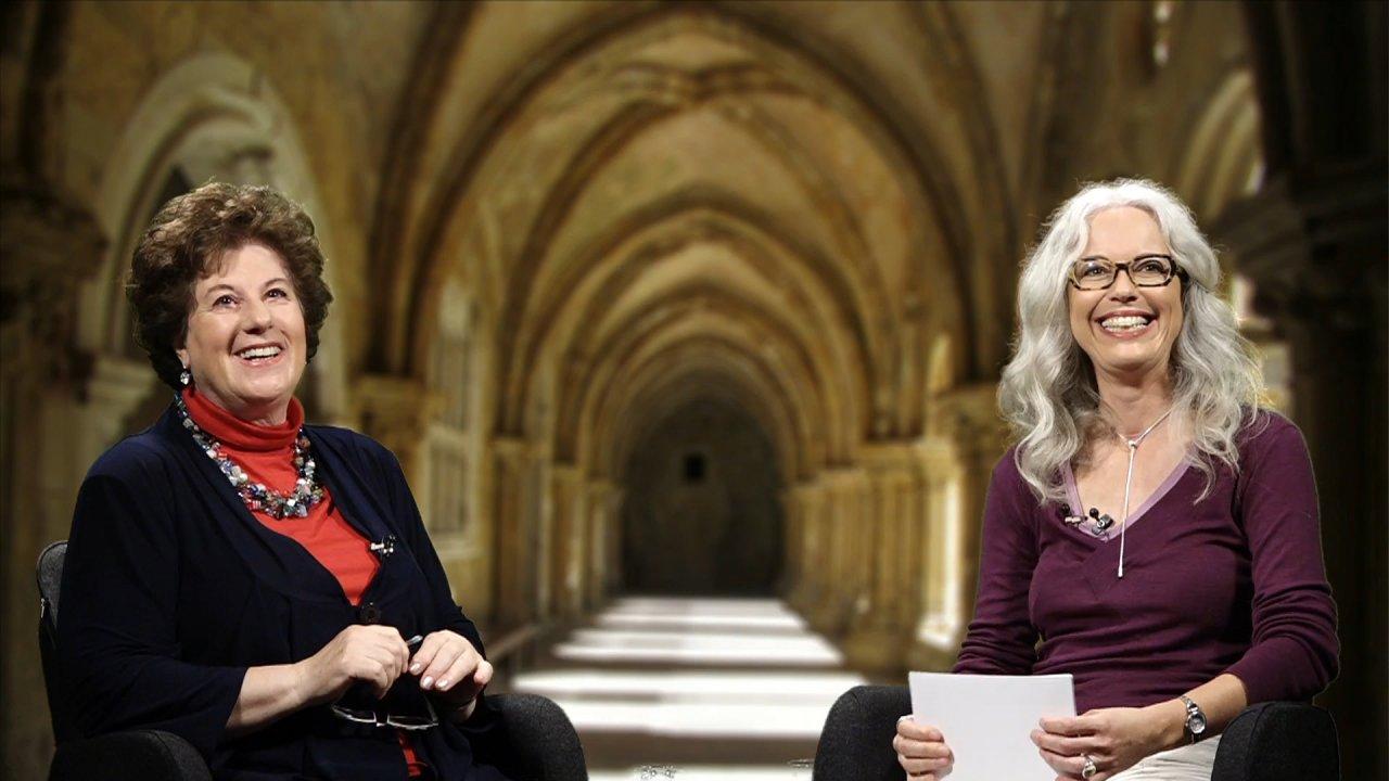 Varda Hasselmann und die Moderatorin sitzen sich in einem Kirchgang gegenüber. Beide lachen und schauen nach oben.