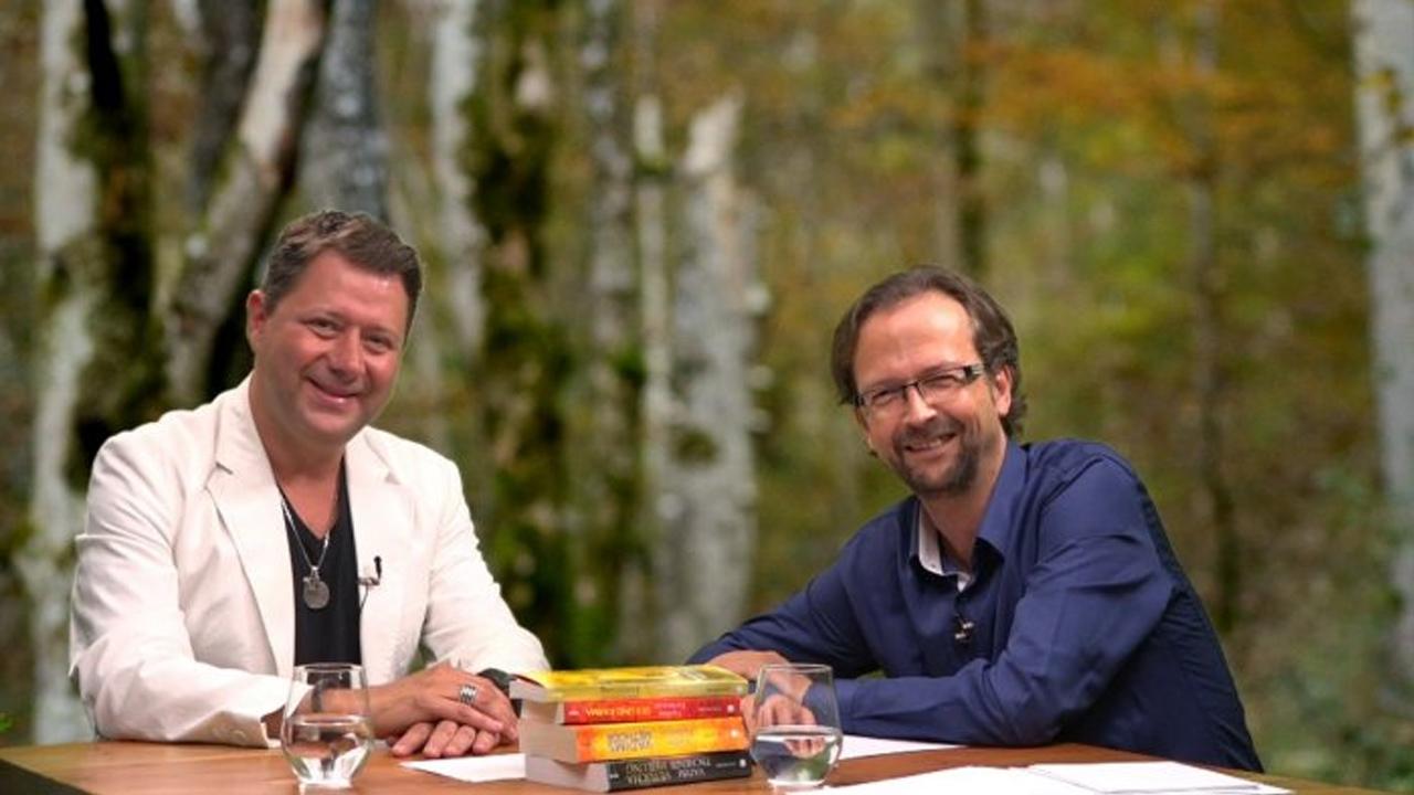 Vadim Tschenze und der Moderator des Webinars sitzen gemeinsam an einem Tisch