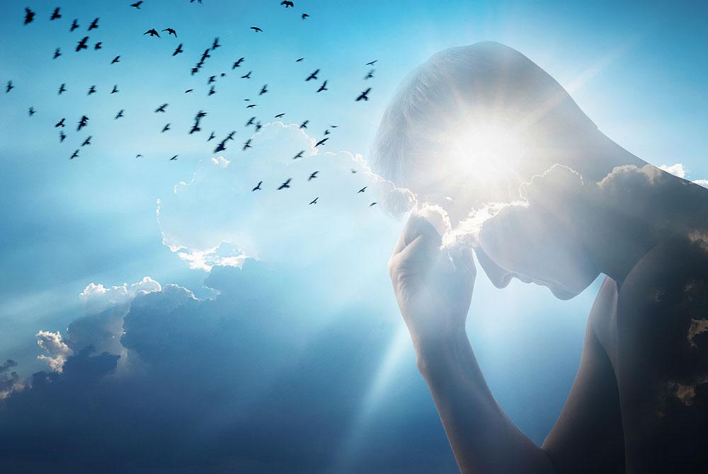 Seitliche Ansicht einer Person, die eine Hand an die Stirn gelegt hat. Es sieht aus wie eine Statue. Im Hintergrund ist ein blauer Himmel mit weißen Wolken zu sehen. Auf Höhe des Kopfes strahlt die Sonne.
