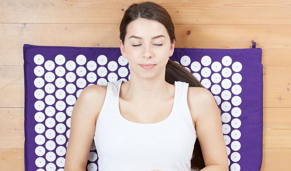 Eine Frau liegt mit geschlossenen Augen und friedlichem Gesichtsausdruck auf einer violetten Akupressur-Matte.