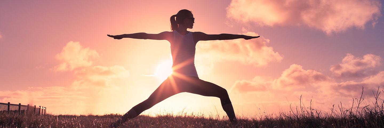 Die Szene zeigt eine Wiese im Sonnenuntergang, auf der eine Person Yoga übt.