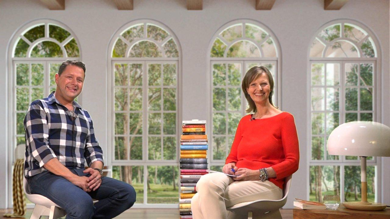 Vadim Tschenze und die Moderatorin des Webinars sitzen sich auf Sesseln gegenüber und schauen freundlich in die Kamera