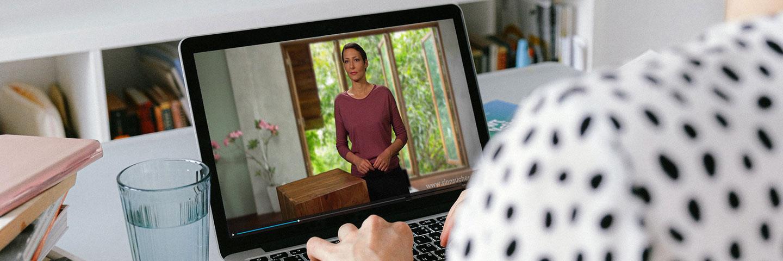 Blick über die Schulter einer Frau, die vor einem aufgeklappten Notebook sitzt und darauf ein Video mit Ina Rudolph anschaut.