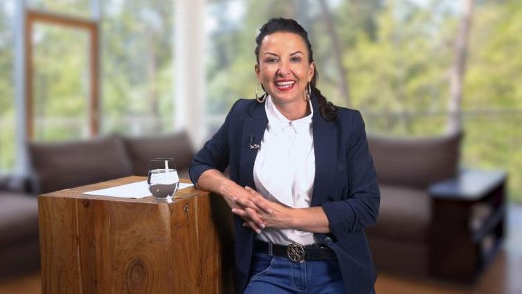 Birgit Jankovic-Steiner lehnt sich an einen Holztisch und blickt fröhlich in die Kamera. Hinter ihr steht ein Sofa.