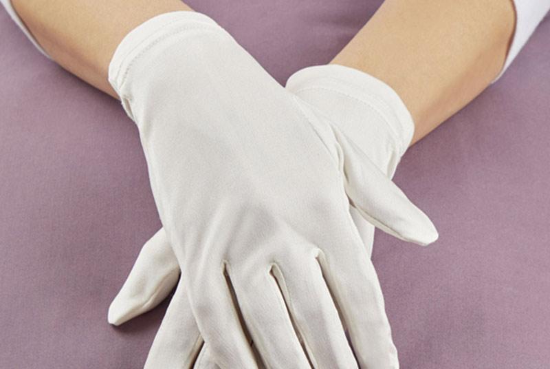 Zwei übereinander gelegte Hände, die in weißen Seidenhandschuhen stecken.