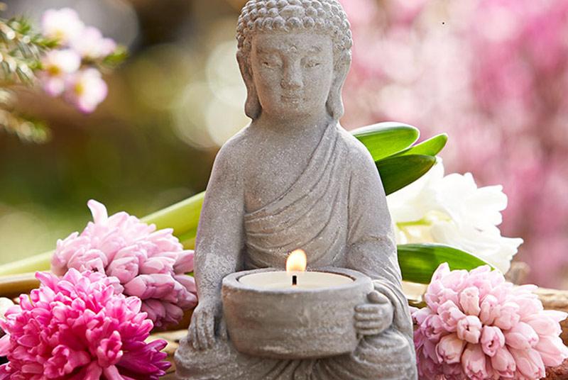 Eine kleine Buddhafigur aus Stein hält ein brennendes Teelicht, hinter ihr liegen rosa und weiße Hyazinthen.