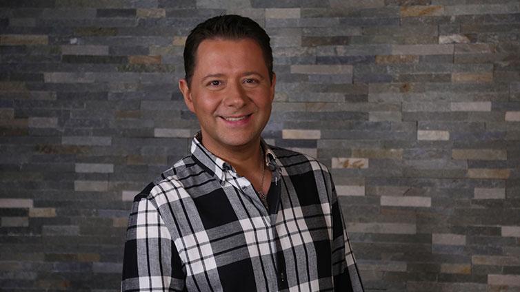 Porträt von Vadim Tschenze. Er trägt ein schwarz-weiß-kariertes Hemd und lächelt breit in die Kamera.