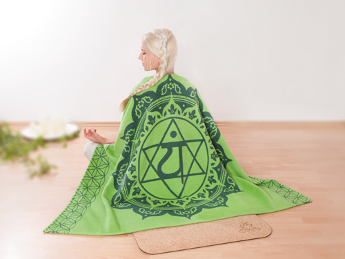 Eine blonde Frau sitzt mit dem Rücken zur Kamera und hat eine grüne Decke umgelegt, auf der das Symbol der Herz-Chakras abgebildet ist