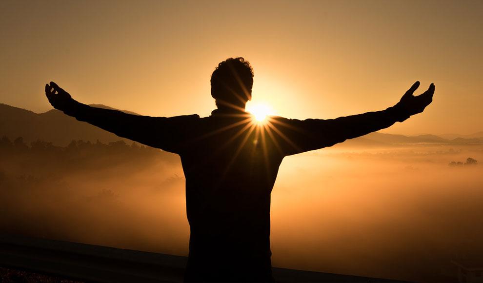 Silhouette eines Menschen mit ausgebreiteten Armen vor der untergehenden Sonne