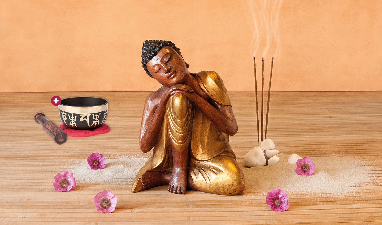 """Hölzerne Buddha-Statue auf einem Holzfußboden umgeben von pinken Blumen. Daneben Räucherstäbchen und das Produkt Klangschale """"OM Mani Padme Hum"""""""