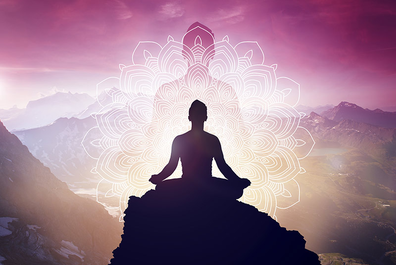 Silhouette eines meditierenden Menschens auf einem Felsen vor einem Bergpanorama.