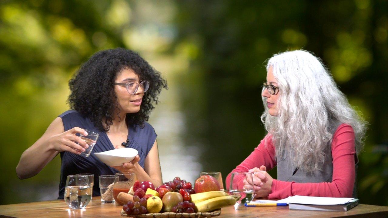 Chantal Sandjon und die Moderatorin sitzen einander zugewandt an einem Tisch, auf dem eine Obstschale steht. Chantal Sandjon hält eine Schüssel und ein Wasserglas in den Händen.