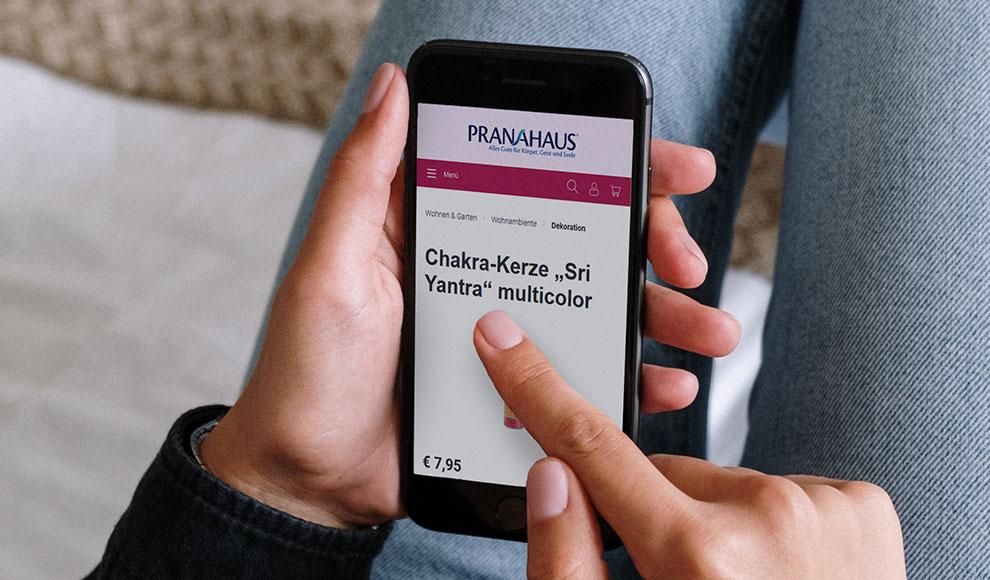 """Eine Hand hält ein Smartphone, auf dem der PranaHaus-Shop aufgerufen wurde. Zu sehen ist die Produktdetailseite des Artikels """"Chakra-Kerze multicolor""""."""