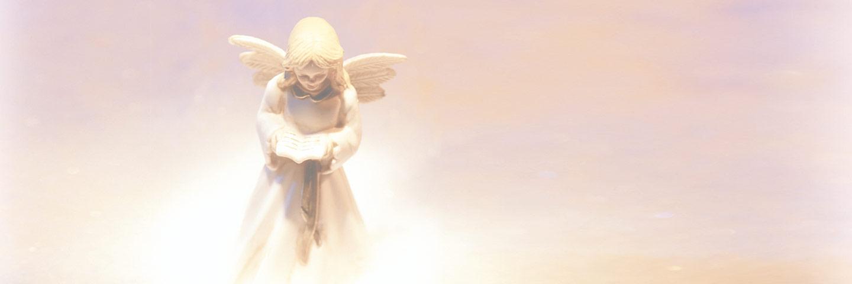 Kleine Engelsfigur aus hellem Stein, die in einem Buch liest