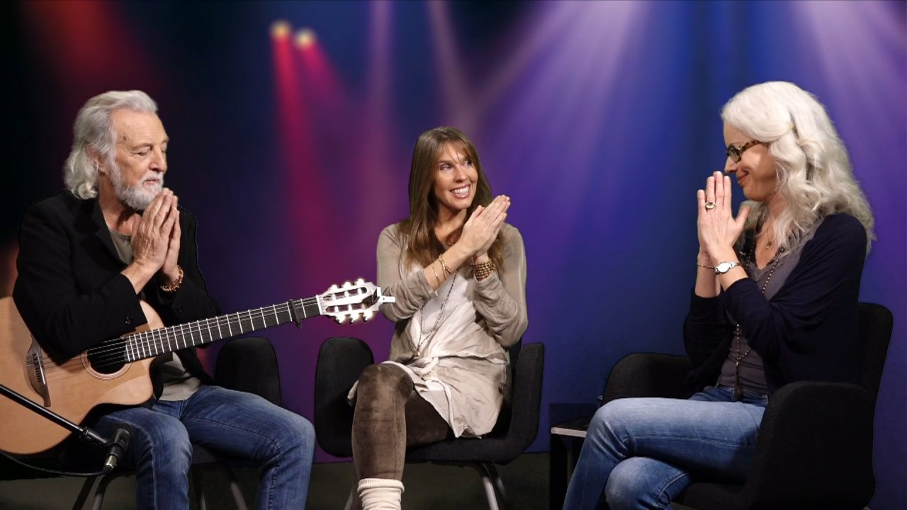 Miten, Deva Premal und die Moderatorin des Webinars sitzen auf Stühlen in einem Halbkreis. Sie haben die Hände in Gebetshaltung aneinander gebracht und schauen einander an. Miten hat eine Gitarre auf dem Schoß.
