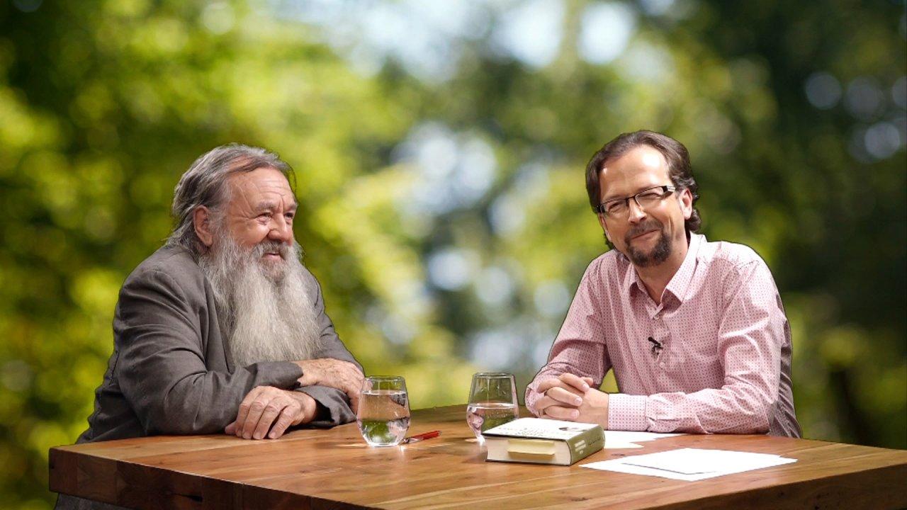 Wolf-Dieter Storl sitzt neben Moderator Thomas an einem Tisch. Thomas blickt in die Kamera.