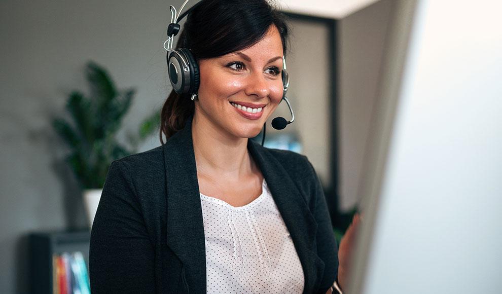 Eine Frau trägt ein Headset und schaut lächelnd auf einen Monitor.