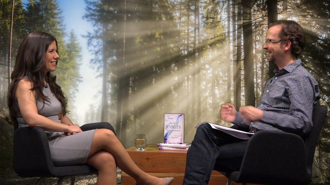 Sue Dhaibi sitzt dem Moderator Thomas gegenüber, sie sind in ein Gespräch vertieft. Auf einem Tisch zwischen ihnen wird Sue Dhaibis Buch präsentiert.