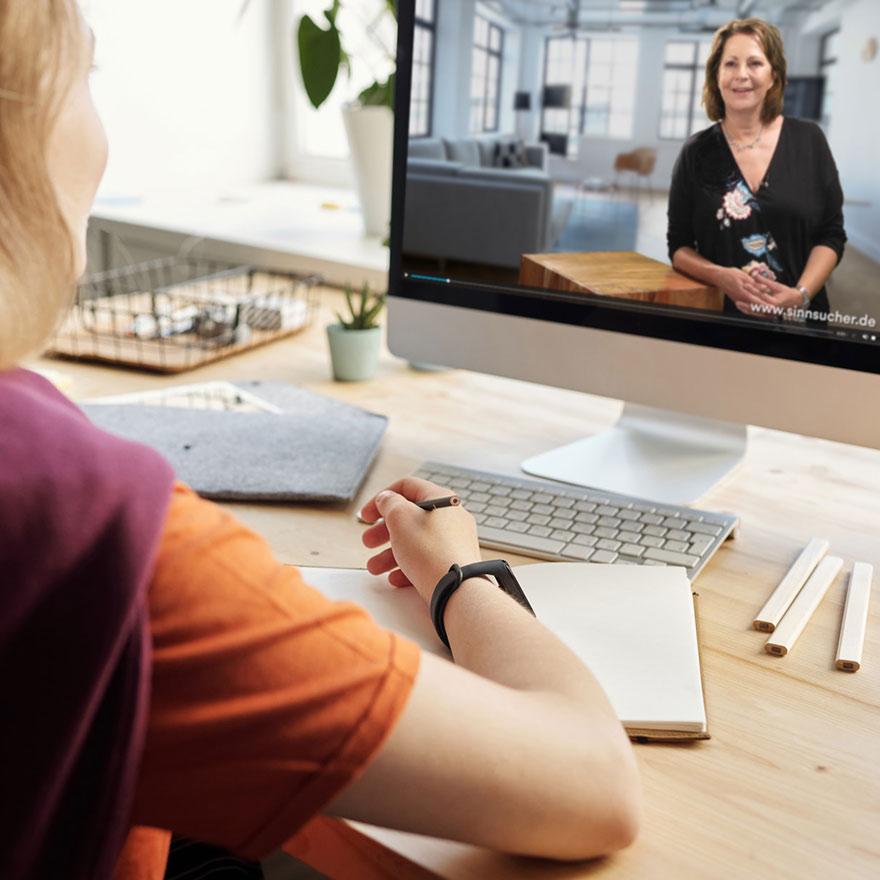 Eine Person sitzt mit dem Rücken zur Kamera vor einem Bildschirm und schaut ein Video zum Online-Kurs mit Stefanie Stahl. Sie hält einen Stift und hat ein Notizbuch bereitgelegt.