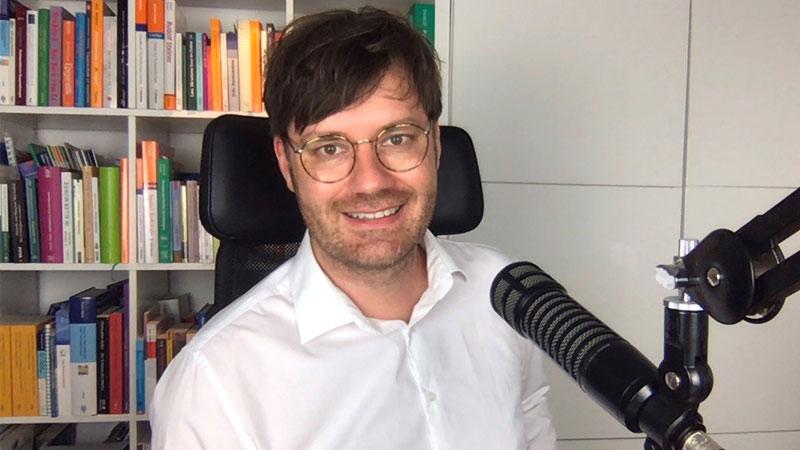 Dr. med. Alexander Kugelstadt trägt ein weißes Hemd und sitzt vor einem Mikrofon. Er lächelt in die Kamera. Im Hintergrund steht ein Bücherregal.